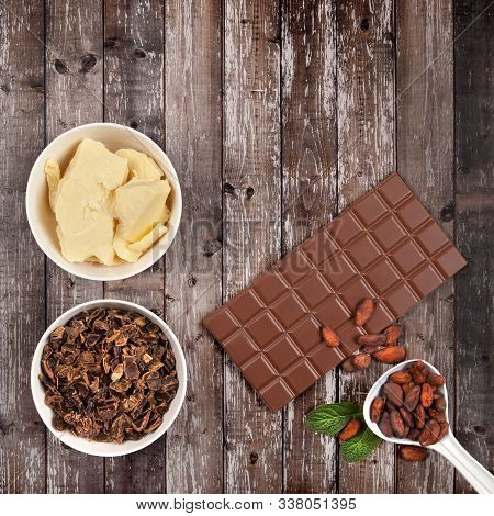 Bar Of Milk Chocolate, Cocoa Butter, Carob, Mint And Cocoa Beans On Dark Wooden Background. Top View