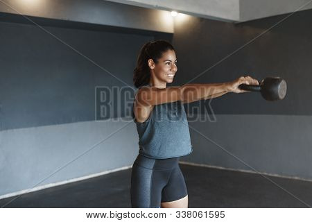 Side-shot Attractive Female Gym Instructor Showing Exercise, Lifting Kettlebell In Front Herself, Sm