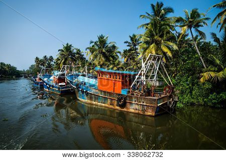Ocean Fishing Boats Along The Canal Kerala Backwaters Shore With Palm Trees At A Sunny Day Between A