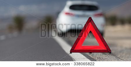 Broken Down Car With Warning Triangle Behind It Waiting For Assistance To Arrive, Red Triangle Of A