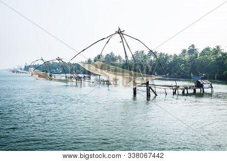 Chinese Fisher Nets Along The Kollam Kottapuram Waterway Along Palm Tree River Shore, Kerala, India