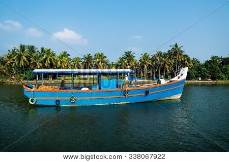 Old Ocean Fishing Boat Along The Canal Kerala Backwaters Shore With Palm Trees At A Sunny Day Betwee