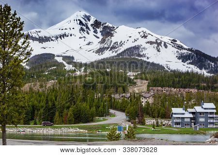 View Of Lone Mountain With Buildings And Pine Trees On The Foot Of The Mountain, Big Sky, Montana, U
