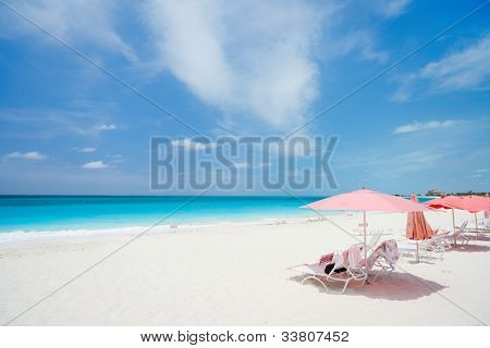 Pink umbrellas on beautiful beach at Providenciales island in Turks and Caicos