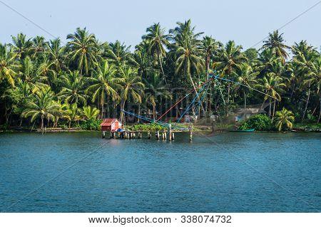 Chinese Fisher Net Along The Kollam Kottapuram Waterway Along Palm Tree River Shore