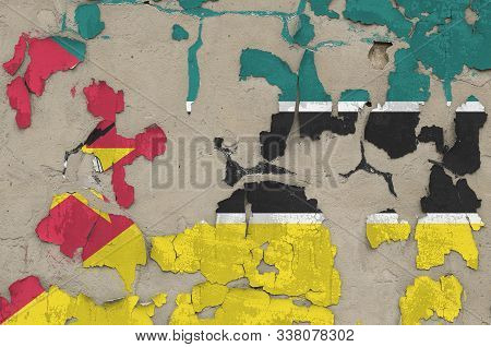 Mozambique flag depicted in paint colors on old obsolete messy concrete wall closeup. Textured banner on rough background poster