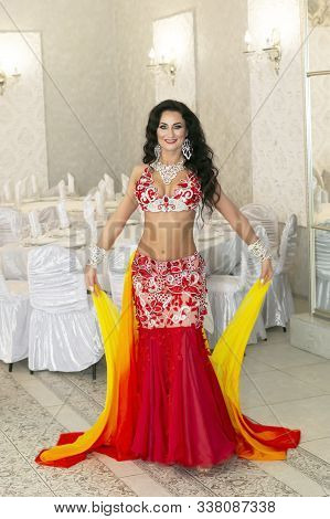Belly Dancer Throws The Ends Of Her Beautiful Orange Skirt Into Air Oriental Dancer In A Red-yellow