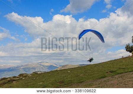 A Paragliding Flying Through The Green Meadows
