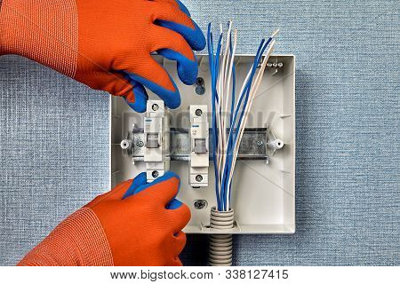 Repair And Upgrade Of Household Wiring. A Repairman In Protective Gloves Installs Circuit Breakers O