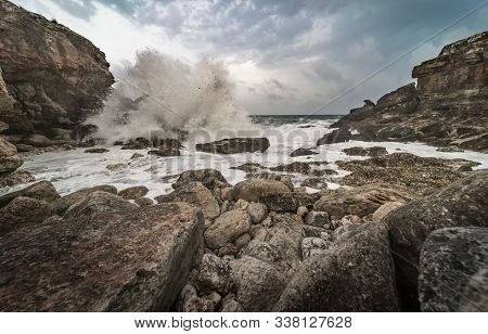 View Of A Wild Cove With Several Rocks, And The Impact Of The Waves On The Rocks In A Rough Sea That
