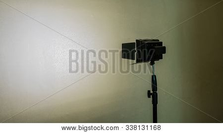 Continuous Led Light Mounted On Tripod Shinning On White Patterned Wall With Deep Shadows.