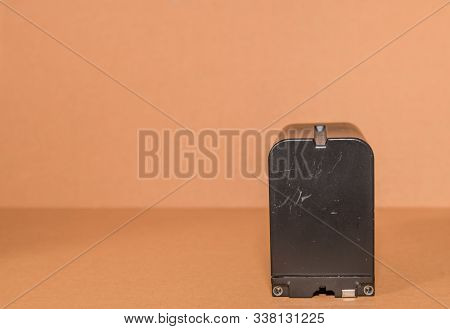 Closeup Side View Of Used Lithium-ion Battery On Brown Background.
