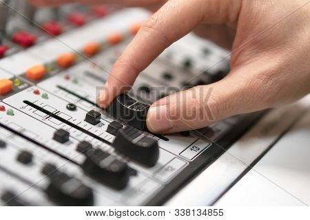 Male Hand On Control Fader On Console. Sound Recording Studio Mixing Desk With Engineer Or Music Pro