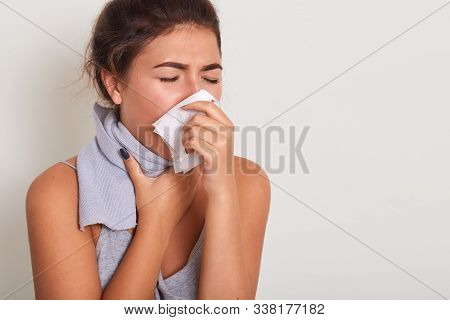 Studio Portrait Of Cute Unhealthy Caucasian Female With Paper Napkin Sneezing, Cathing Cold, Attract
