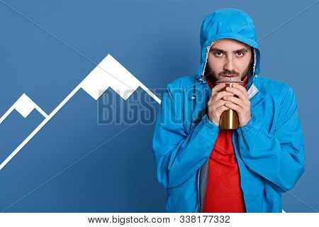 Serious Sad Bearded Man Basking Hands With Thermo Mug Of Tea Or Coffee, Dresses Blue Coat And Red Sh