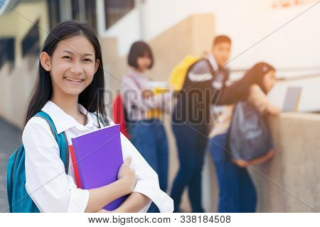 Young Student Teenager Girl High School Student Carrying Schoolbag Holding Notebooks With Friends In