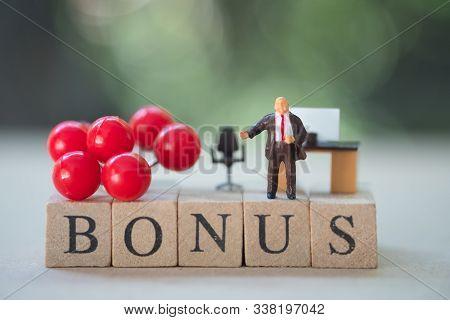 Miniature People: Boss Standing On Wooden Block Of Bonus. Bonus Prize Profit Incentive Additional Co