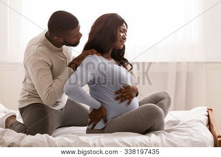 Pregnant Black Woman Suffering From Back Pain, Sitting On Bed, Her Husband Massaging Her Shoulders,