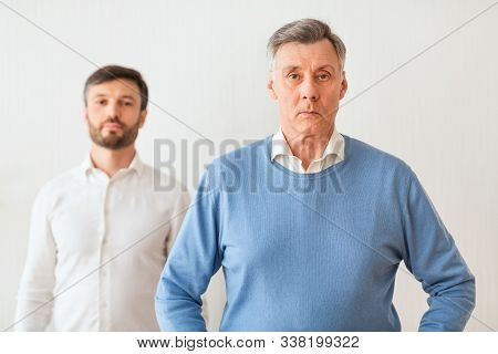 Authoritarian Parent. Serious Mature Son Standing Overshadowed By His Elderly Father Looking At Came