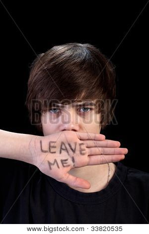 Teenager refusing help looking angry - on black background