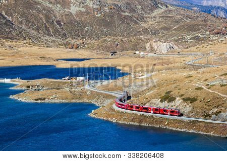 Grisons, Switezrland - October 21.02018: The Bernina-train Is Curving Along The Glacier Lake Bianco