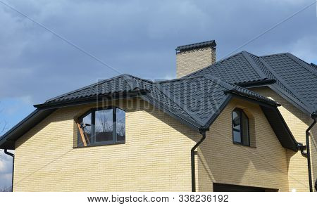Valley And Gable House Ceramic Tiled Roofing Construction With Gutter Pipeline. Brick House With Pro