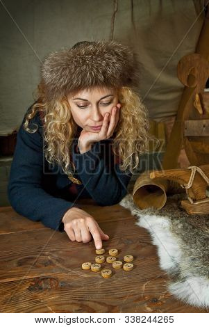 Girl With Blue Eyes Wonders On The Runes. Blonde In A Viking Costume At The Middle Ages Festival. Au
