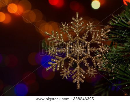 Gold colored glittery snowflake shaped Christmas ornament in tree, with bright colorful bokeh light background