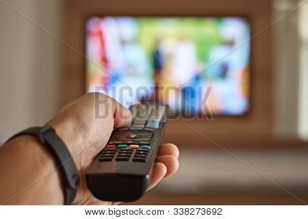 Man Watching Tv In The Room And Switches Channels Using The Remote Control In His Hand