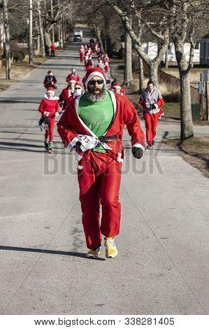 Mattapoisett, Massachusetts, Usa - December 7, 2019: Colorful Santa Leading Horde Of Runners To Fini