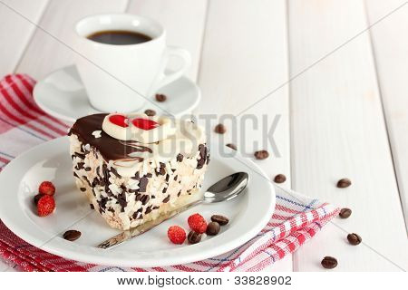 sweet cake with chocolate on plate and cup of coffee on wooden table