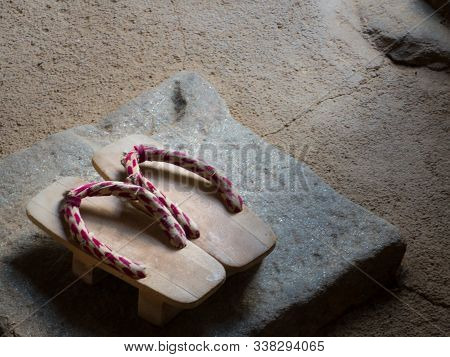 Traditional Japanese Wooden Geta Shoes Standing On Stone Entrance Steps To Temple. Still Life Of Old
