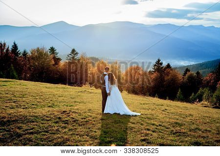 Beautiful Wedding Couple, Bride And Groom, In Love On The Background Of Mountains. The Groom In A Be