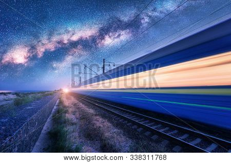 High Speed Train In Motion And Milky Way At Starry Night. Industrial Landscape With Sky And Stars Ov