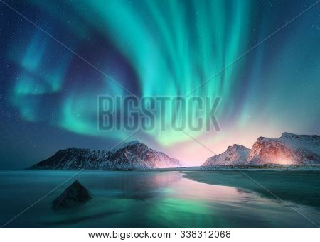Aurora Borealis Over The Sea, Snowy Mountains And City Lights At Night. Northern Lights In Lofoten I