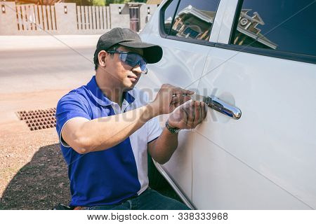 Young Man Opening White Car Door With Lockpicker. Professional Making Key In Locksmith