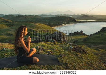 Woman Doing Yoga Alone At Sunrise With Mountain And Ocean View. Harmony With Nature. Self-analysis A