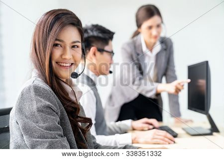 Young adult friendly and confidence operator woman agent smiling with headsets working in a call center with her colleague team working as customer service and technical support workplace .