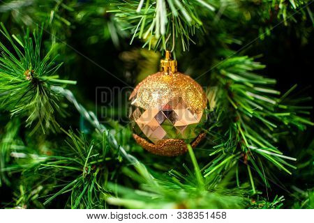 Gold Bauble Among Chistmas Tree Brenches. Closeup Look Of The Ball.