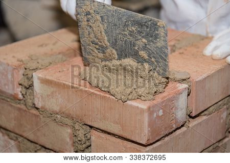 Bricklayer Works With Smoothing Trowel While Building A Bricks Wall - Close-up