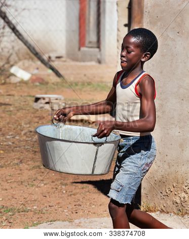 African child portrait in a village in the rural  Botswana carry heavy container with water , in front of the house