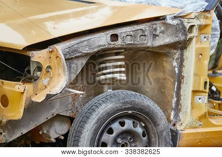 Front part of a wrecked car wreck with suspension spring above the wheel