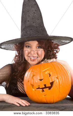 Teen Girl In Halloween Hat With Carved Pumpkin