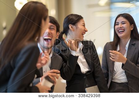 Asian Business People Talking And Laughing In Office Building. Young Businessman And Businesswoman C