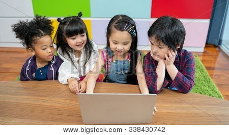 Group Of Little Children Diversity Watching Film Together On Laptop. Kids Playing With Laptop Comput