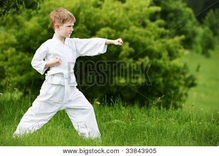 One little boy in white kimono during training karate kata exercises in summer outdoors