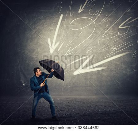 Determined Businessman Hiding Behind Umbrella As A Shield To Protect Of Any Danger And High Pressure