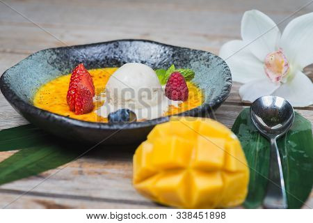 Traditional Dessert Cream Catalana And Creme Brulee In A Beautiful Plate On A Wooden Table In A Rest