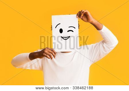 Black Guy Holding Paper With Positive Emoji Over Orange Background, Hiding His Real Emotions