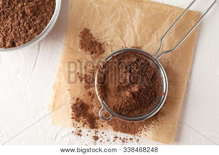 Glass Bowl And Strainer With Cocoa Powder, Baking Paper On White Background, Close Up